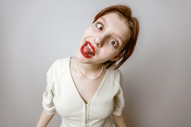 Het meisje trekt een grimas, trekt haar tong uit en tuurt