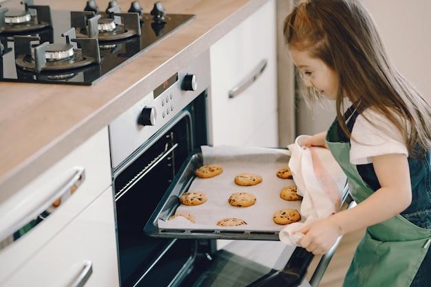 Het meisje trekt een koekjesdienblad uit de oven