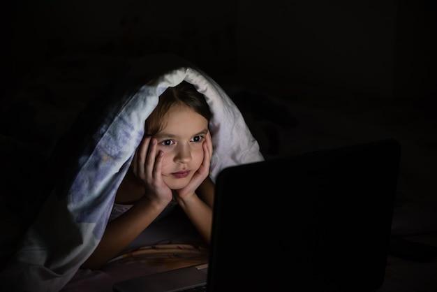 Het meisje van 9 jaar oud is 's nachts bedekt met een deken en onderzoekt een laptop.
