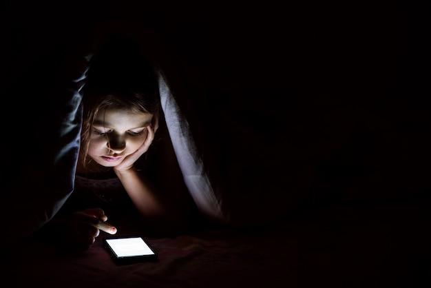 Het meisje van 9 jaar oud is 's nachts bedekt met een deken en onderzoekt een smartphone.