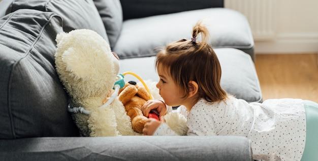 Het meisje van de babypeuter het spelen met van de arts uitrusting en pop speelgoed