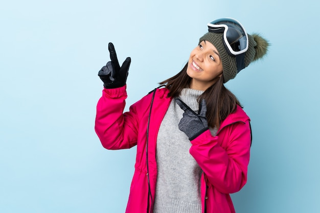 Het meisje van de gemengd rasskiër met snowboarding glazen op geïsoleerd blauw die met de wijsvinger een groot idee richten