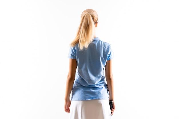 Het meisje van de het tennisspeler van de tiener over geïsoleerde witte muur