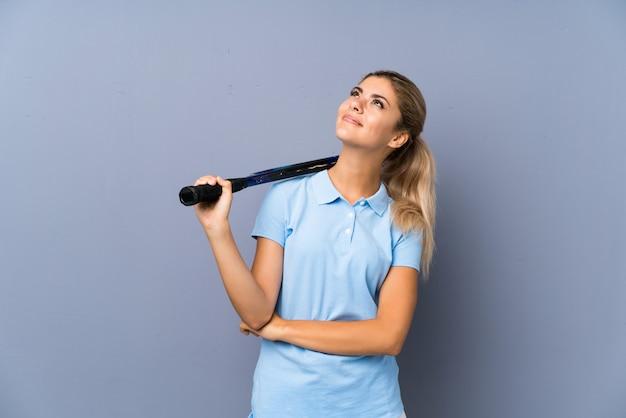 Het meisje van de het tennisspeler van de tiener over grijze muur die omhoog terwijl het glimlachen kijkt