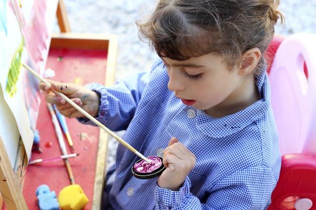 Het meisje van de kunstenaarsschool het schilderen waterverfportret
