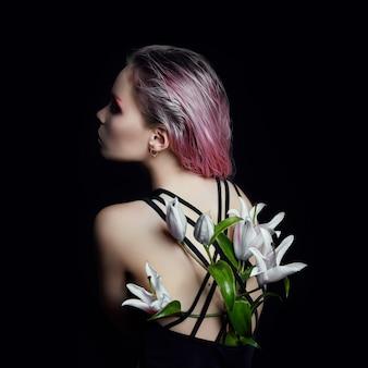 Het meisje van de kunstschoonheid met erachter lelies op een zwarte
