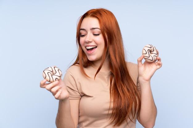 Het meisje van de roodharigetiener over geïsoleerde blauwe muurholding donuts met gelukkige uitdrukking