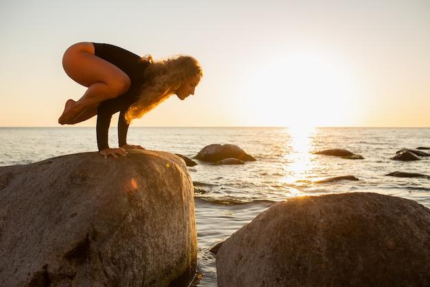 Het meisje van de silhouetyoga door het strand bij zonsopgang die crane pose doen. langharig meisje dat yogapraktijk op een grote steen doet. bakasana.