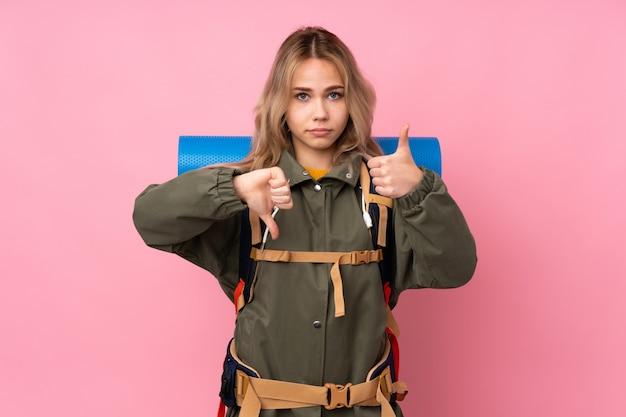 Het meisje van de tienerbergbeklimmer met een grote die rugzak op roze wordt geïsoleerd dat goed-slecht teken maakt. onbeslist tussen ja of niet