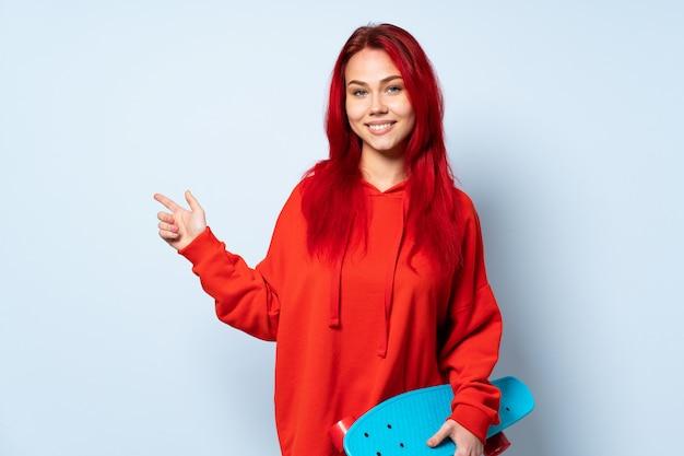Het meisje van de tienerschaatser dat op witte achtergrond wordt geïsoleerd die vinger aan de kant richt