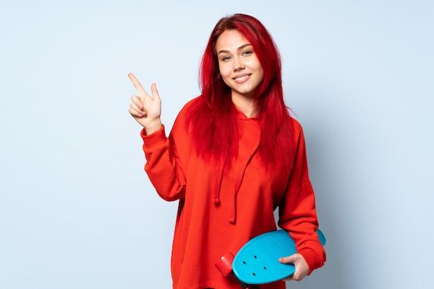 Het meisje van de tienerschaatser op witte zij wijzende vinger wordt geïsoleerd die als achtergrond en gelukkig die