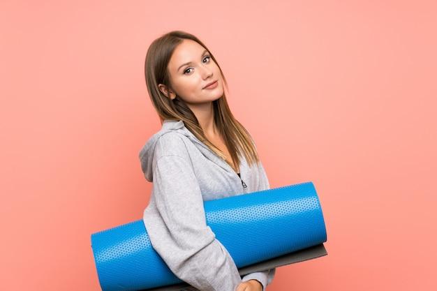 Het meisje van de tienersport met mat over geïsoleerde roze achtergrond