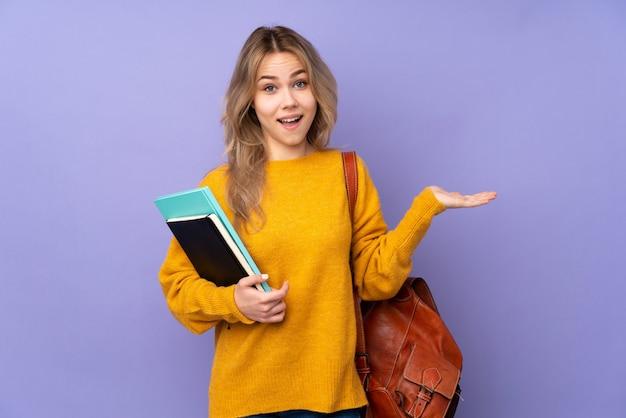 Het meisje van de tienerstudent op purpere muur met geschokte gelaatsuitdrukking wordt geïsoleerd die