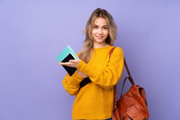 Het meisje van de tienerstudent op purple die een idee voorstellen terwijl het kijken naar glimlachen
