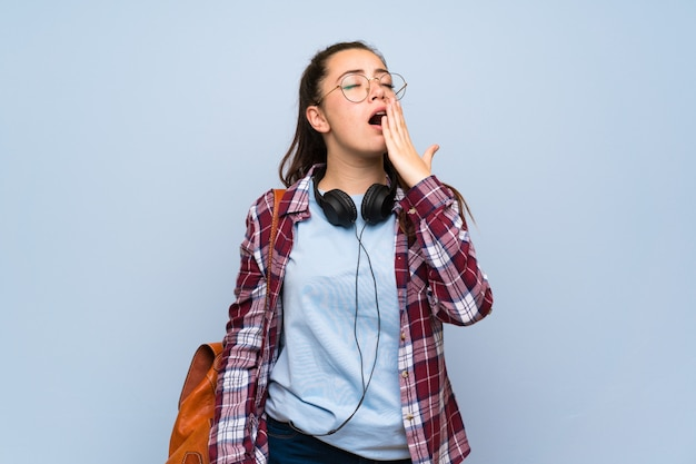Het meisje van de tienerstudent over geïsoleerde blauwe muur die en wijd open mond geeuwen behandelen met hand