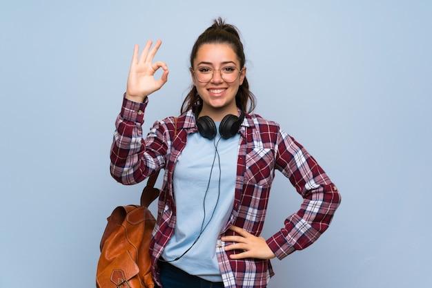 Het meisje van de tienerstudent over geïsoleerde blauwe muur die ok teken met vingers tonen