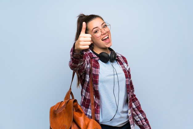 Het meisje van de tienerstudent over geïsoleerde blauwe muur met omhoog duimen omdat er iets goeds is gebeurd