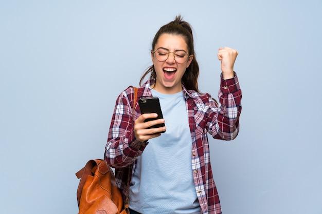 Het meisje van de tienerstudent over geïsoleerde blauwe muur met telefoon in overwinningspositie