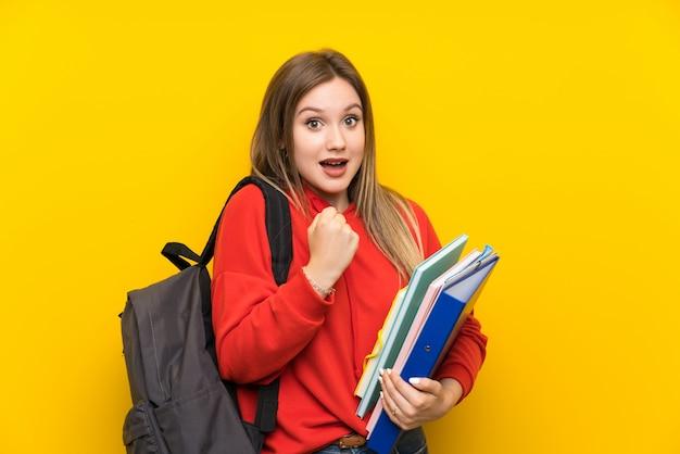 Het meisje van de tienerstudent over gele muur die een overwinning vieren