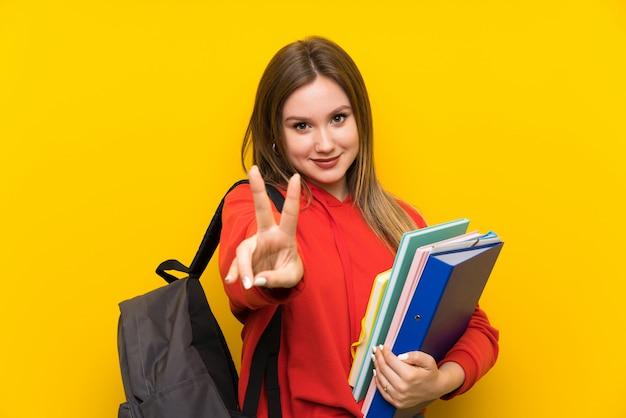 Het meisje van de tienerstudent over gele muur die en overwinningsteken glimlachen tonen