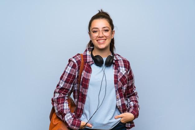 Het meisje van de tienerstudent over het geïsoleerde blauwe muur lachen