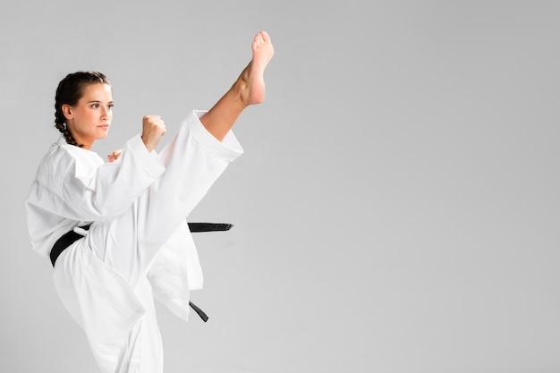 Het meisje van de vechtsportenkarate met zwarte band en exemplaar ruimteachtergrond