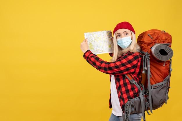 Het meisje van de vooraanzichtreiziger met haar rugzak die kaart steunt