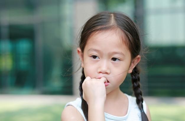 Het meisje van het kind is van plan haar vingers te zuigen. de gebaren van kinderen die geen vertrouwen hebben.