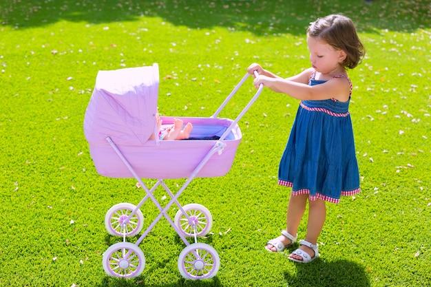 Het meisje van het peuterjonge geitje het spelen met babykar in groen gras