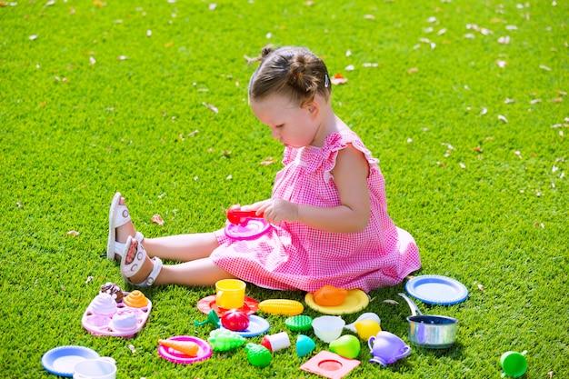 Het meisje van het peuterjonge geitje spelen met voedselspeelgoed die in gras zitten