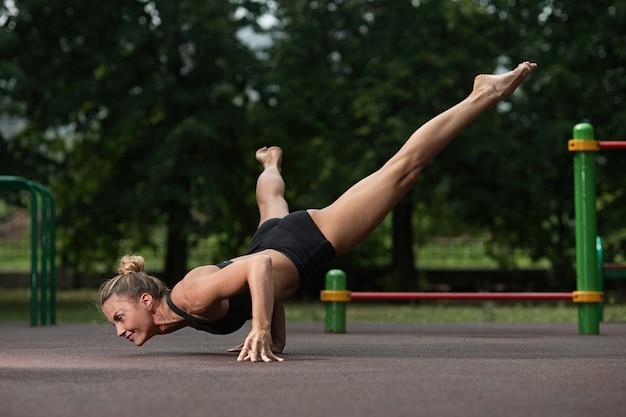 Het meisje van sportenacrobatiek bevindt zich op haar handen en maakt een acrobatisch element