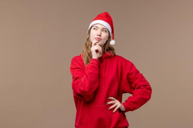 Het meisje van vooraanzichtkerstmis met denkend gezicht op de bruine achtergrondvakantie nieuwe jaar kerstmis