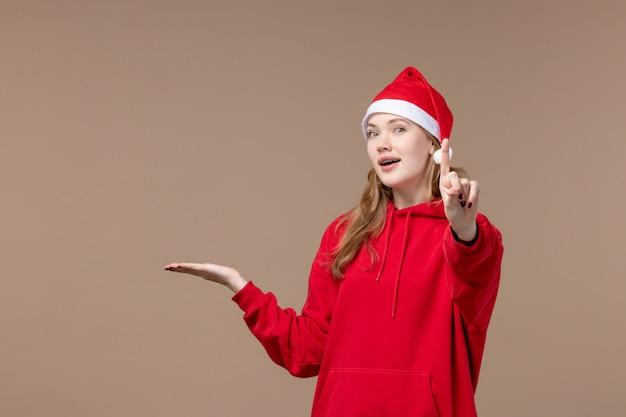 Het meisje van vooraanzichtkerstmis met rode cape op bruine kerstmis van het bureauvakantie nieuwe jaar