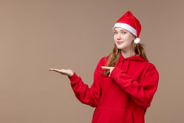 Het meisje van vooraanzichtkerstmis met rode cape op de bruine ruimte