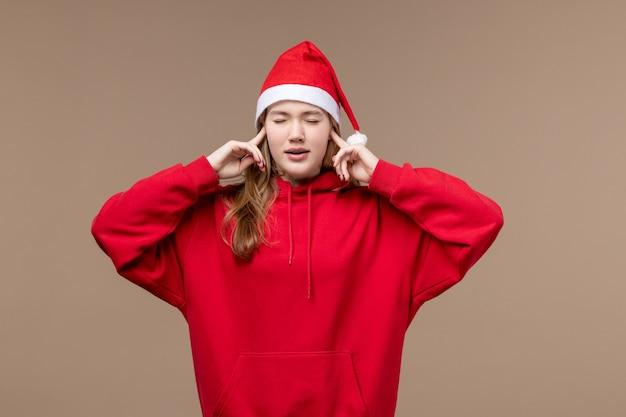 Het meisje van vooraanzichtkerstmis sluit haar oren op bruine achtergrond modelvakantiekerstmis
