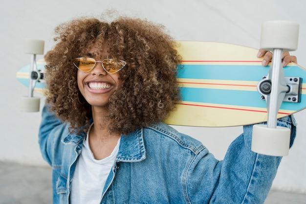 Het meisje van zijaanzichtsmiley met skateboard