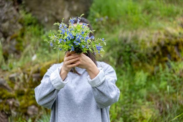 Het meisje verbergt haar gezicht achter een boeket verse bloemen verzameld in het bos.