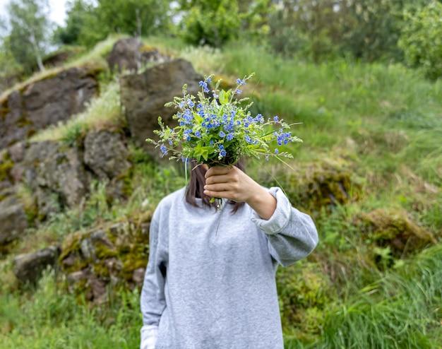 Het meisje verbergt haar gezicht achter een boeket verse bloemen verzameld in het bos