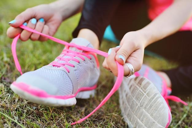 Het meisje verbindt schoenveters op tennisschoenen alvorens te lopen of vóór geschiktheidstraining op van van aard