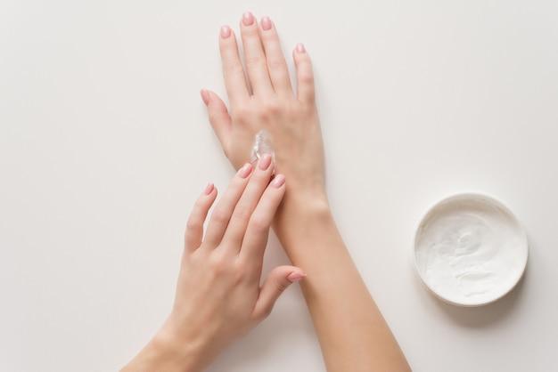 Het meisje verdeelt vochtinbrengende crème op haar handen.