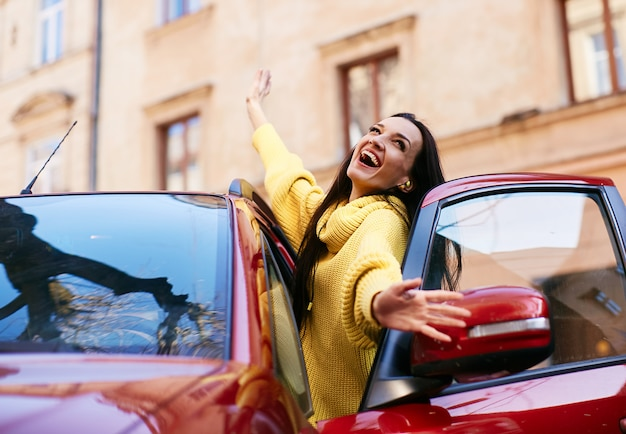 Het meisje verheugt zich in het leven en zit in haar rode auto