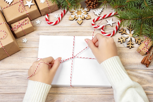 Het meisje verpakt kerstmisbrieven in envelop, de brief van de kerstmissanta in envelop, kerstmisachtergrond