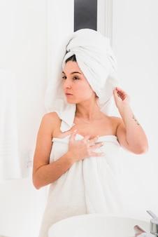 Het meisje verpakte haar haar en lichaam in een handdoek kijkend in spiegel