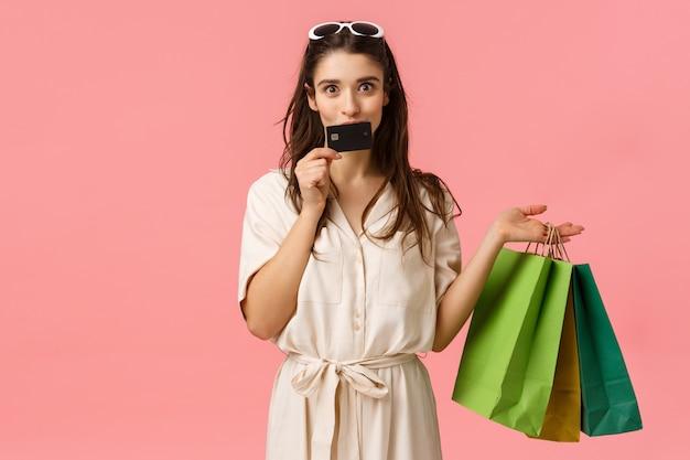 Het meisje verspilt graag geld aan haar creditcard, kust het en glimlacht vrolijk, draagt boodschappentassen, winkelt in winkels, krijgt nieuwe kleren, bereid cadeaus voor vriendinnen voor, staat op roze achtergrond