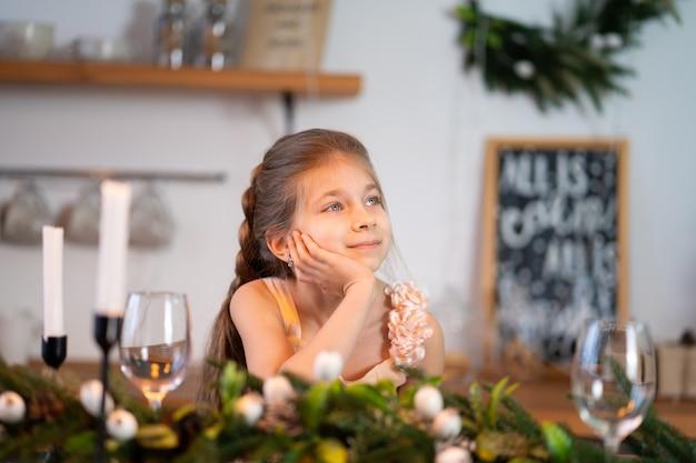 Het meisje verveelt zich tijdens de kerstnacht aan de feesttafel.