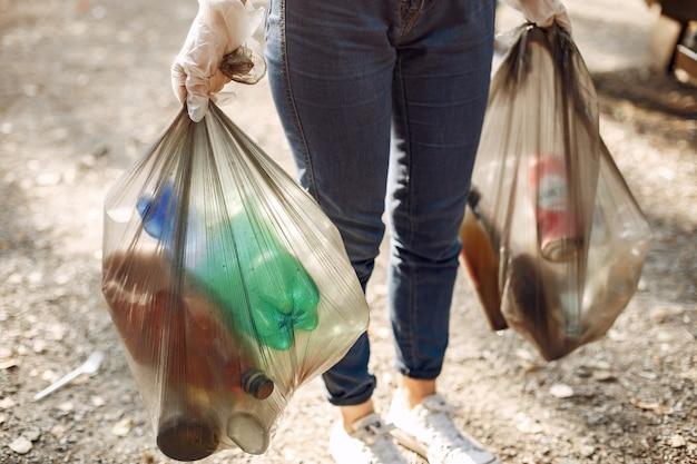 Het meisje verzamelt afval in vuilniszakken in park