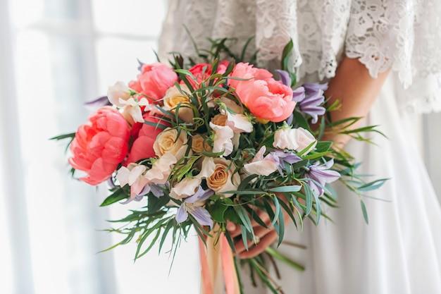 Het meisje verzamelt een boeket van prachtige bloemen: roos, pioenroos, lila, narcis