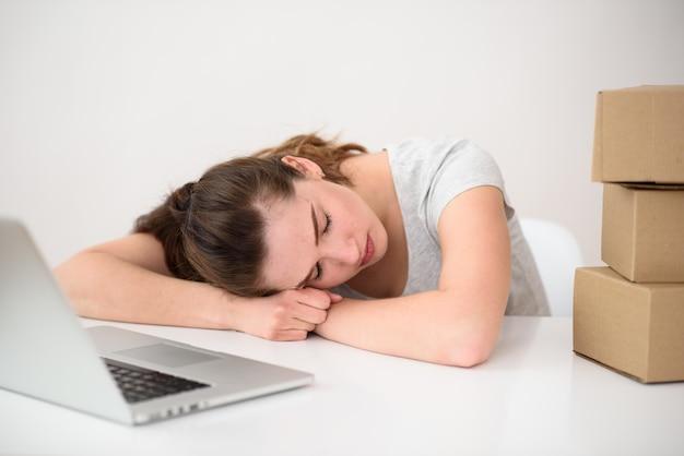 Het meisje viel in slaap aan een tafel tegenover een laptop en dozen. moe na het werk. non-stop werk