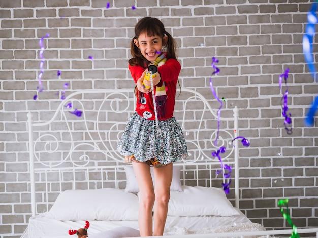 Het meisje viert en gooit kleurrijke confetti in zijn bed