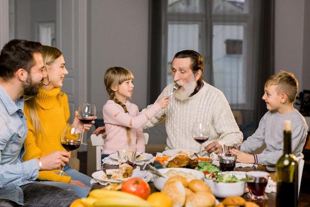 Het meisje voedt haar oude grootvader en geeft hem smakelijke pasta, glimlachend en lachend